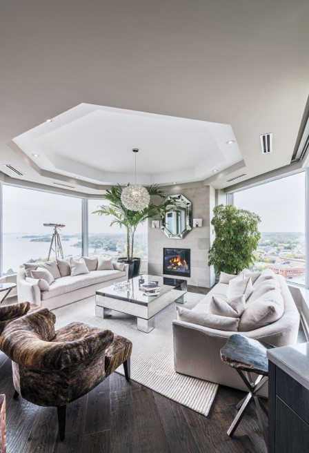 The elegant formal living room seating area boasts oversized windows on three sides and offers spectacular northerly and westerly vistas. The space seems to shimmer in tones of silver, grey, and cream. Photo by Christian Lalonde