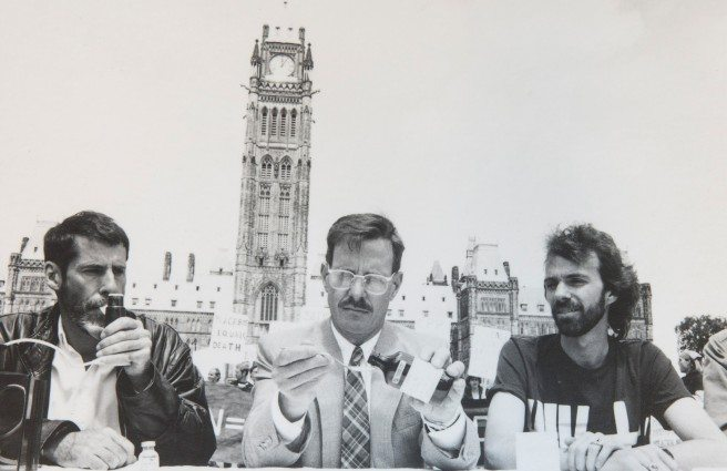 PARLIAMENT HILL PROTEST — From left: in 1988, Bill Greenway, Michael Lynch, and James Thomas — members of AIDS Action Now — demonstrated the government's inaction in making experimental HIV/AIDS drugs available by taking four. Photo: Colin Rowe, courtesy of ACO of the 24 drugs already available elsewhere in th